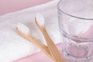 Wooden toothbrushes with glass and towel