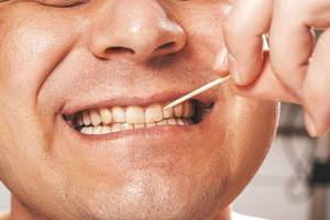 Wooden toothpick and white healthy teeth of a man (Flip 2019)