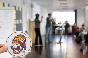 WordCamp 2017 Sticker und eine Präsentation im Hintergrund