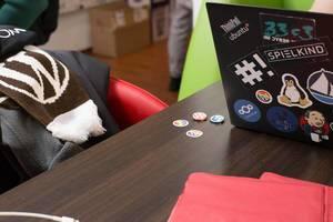 Wordpress Broschen, Schal und ein ThinkPad mit vielen Stickern auf dem Rückdeckel
