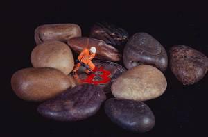 Worker standing on Bitcoin between rocks