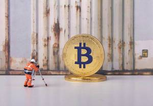 Worker taking photo of a golden Bitcoin
