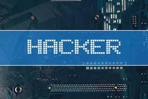 Wort Hacker vor einer elektronischen Leiterplatte als Hintergrund