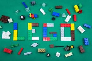 Wort LEGO, gebildet aus Legosteinen zwischen Legofiguren und bunten Legosteinen auf grünem Hintergrund