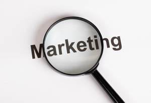 Wort Marketing unter einer Lupe mit weißem Hintergrund
