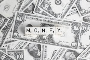 Wort MONEY (Geld) gebildet aus Würfel auf Hintergrund aus US-Dollar Banknoten