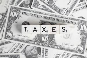 Wort TAXES (Steuern) mit Würfel gebildet auf verteilten US-Dollar Banknoten