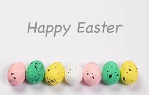 Worte FROHE OSTERN über eingefärbten Ostereiern in gelb, rosa und grün vor weißem Hintergrund