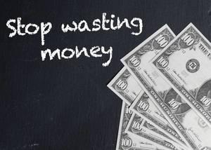 Worte STOP WASTING MONEY (keine Geldverschwendung) und US-Dollar Noten