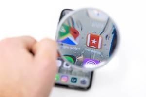 Wunderlist App auf Smartphone durch Lupe betrachtet vor weißem Hintergrund