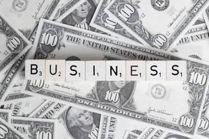 Würfel bilden das Wort BUSINESS (Geschäft) auf US-Dollar Banknoten