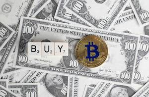Würfel bilden das Wort Buy neben Bitcoin Münze auf US-Dollar Banknoten