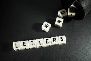 """Würfel bilden das Wort """"Letters"""" - Buchstaben - neben herausfallenden Würfeln aus einem dunklen Würfelbecher"""