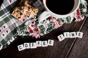 """Würfel ergeben den Begriff """"Coffee Time"""" - Kaffeezeit,  neben einer Tasse mit schwarzem Kaffee und einem Müsliriegel"""