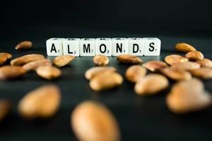 Würfel mit Buchstaben bilden das Wort ALMONDS vor geschälten Mandelkernen