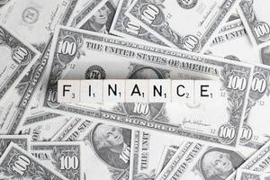 Würfel mit Buchstaben bilden das Wort FINANCE (Finanzen) auf Hintergrund aus Banknoten
