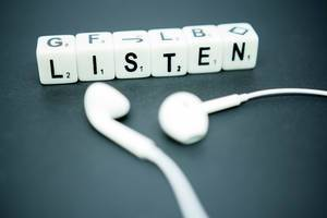 Würfel mit Buchstaben bilden das Wort LISTEN neben weißen Kopfhörern