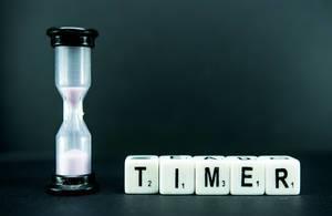 Würfel mit Buchstaben bilden Wort TIMER neben kleiner Sanduhr vor dunklem Hintergrund