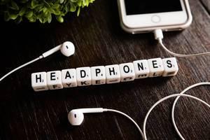 """Würfel zeigen das Wort """"Headphones"""" - Kopfhörer, neben einem weißen Iphone auf einem Holztisch"""