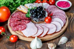 Wurstteller mit frischer Salami und geräuchertem Schinken, präsentiert zwischen frischem Gemüse und Knoblauch auf einem Holztisch