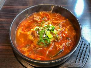 Würziger Eintopf mit Rindfleisch, Reis und Gemüse in schwarzem Topf auf Holztisch
