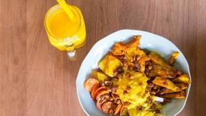 Yellow Bowl mit Safran Bulgur, Süßkartoffel, Pastinaken, gebackene Kichererbsen, Kaki, Sesam-Möhren, geröstete Erdnüsse, Kürbis-Hummus, Kurkuma Tahini-Dressing