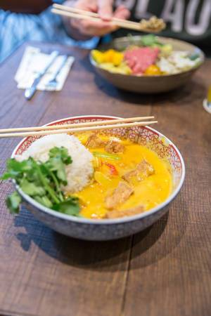 Yellow coconut tofu curry as vegan Asian lunch with Jasmin fragrant rice and baby spinach, in a traditional bowl with chopsticks, on a wooden table
