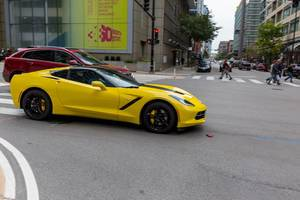 Yellow Corvette sports car at an intersection in Downtown Chicago