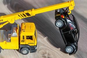 Yellow crane pulls black car - kids toys