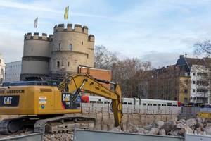 Yellow crawler excavator lift an excavation behind at Cologne Rudolfplatz