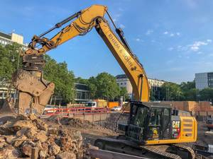 "Yellow excavator works on a construction site for the new office tower ""Wallarkaden"" next to U-Rudolfplatz and Hahnentor in Cologne"