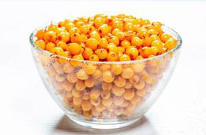 Yellow fresh sea buckthorn berries in glass bowl
