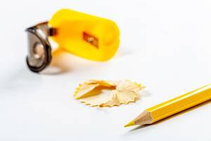 Yellow pencil, sawdust and pencil sharpener on white background (Flip 2019)