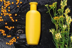 Yellow plastic bottle and sea buckthorn berries and wildflowers on black background. Natural care products (Flip 2019)