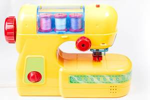 Yellow plastic sewing machine-toy for children on a white background (Flip 2020)