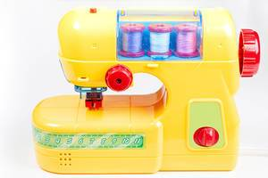 Yellow plastic sewing machine-toy for children on a white background