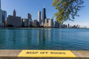 "Yellow warning sign: ""Keep off rocks"" by the waters of Lake Michigan in Downtown Chicago"