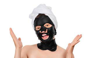 Young beautiful woman in a black mask for the face