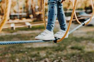 Young girl walking on rope in rope park. Legs detail
