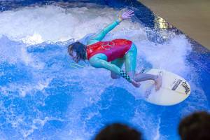 Young man trying out the surf machine Citywave at fair Boot Düsseldorf 2018