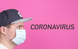 Young man with medical flu mask and Coronavirus text