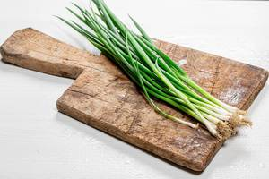 Young onions on an old wooden kitchen Board