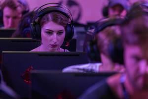 Young woman gaming at Gamescom 2018