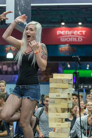 Young woman high fives after winning at Jenga tower game at Gamescom 2018