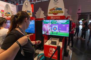 Young woman tests virtual archery sports of the video game Mario&Sonic at The Olympic Games, at the Nintendo Switch game station at Gamescom