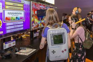 Young women playing Taiko Drum Master for Nintendo Switch at Gamescom
