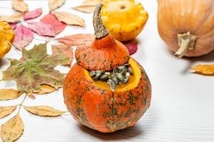 Yummy Halloween pumpkin with seeds on a white wooden background with autumn yellow leaves (Flip 2019)