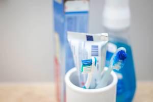 Zahnbürsten mit Zahnpaste in einem Becher - Badezimmer