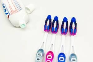 Zahnbürsten und Zahnpasta auf einer weißen Oberfläche