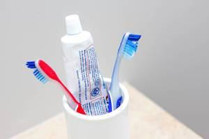 Zahnbürsten und Zahnpasta in weißer Tasse
